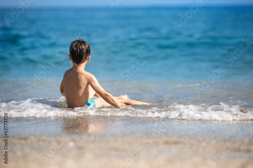 Little boy splashing in ocean waves