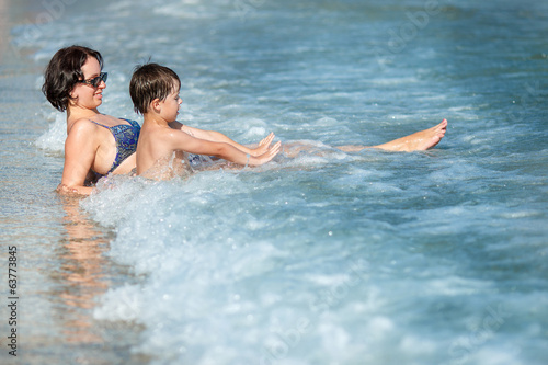 Mother and son splashing in ocean waves