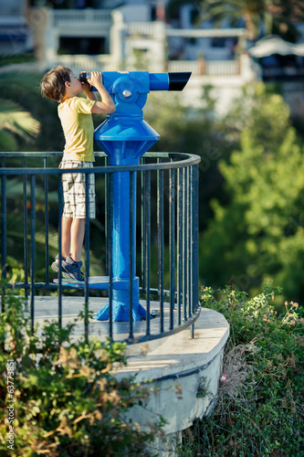 Child looking through coin operated binoculars