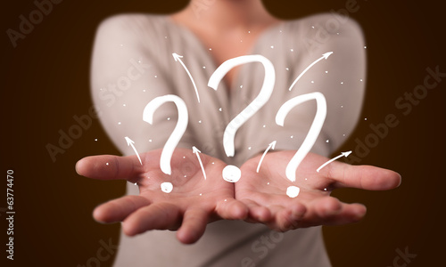 Young woman presenting hand drawn question marks