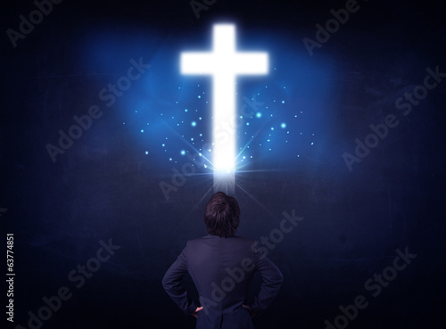 Businessman in front of a glowing cross