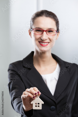 Young businesswoman giving house keys.