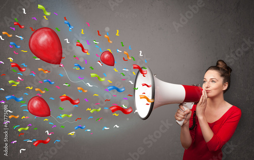 Young girl having fun, shouting into megaphone with balloons