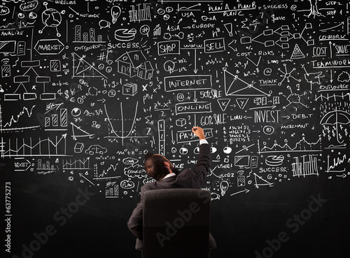 Businessman sitting in front of a blackboard with charts