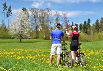 Travelers with mountain bikes in a meadow