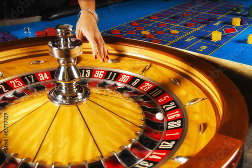 Roulette wheel and croupier hand.