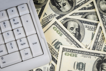 Keyboard on background of one hundred dollars notes