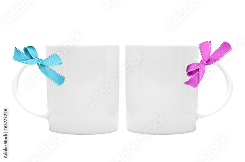 Two white cup with ribbon bow on white background