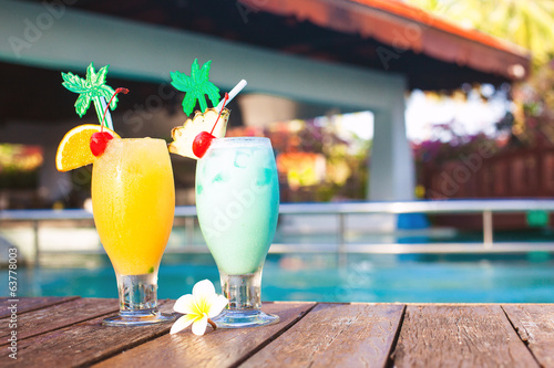 two glasses of cocktails and flower near pool. party