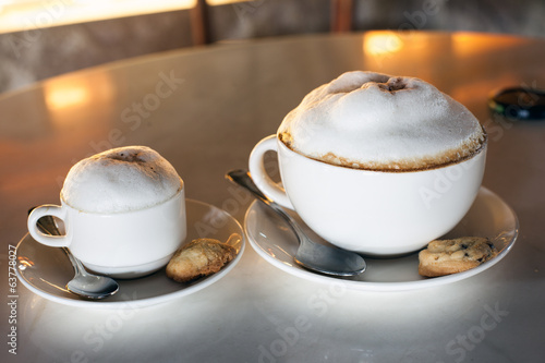 Two cups of cappuccino on table