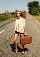 Woman with suitcase, hitchhiking along a countryside road