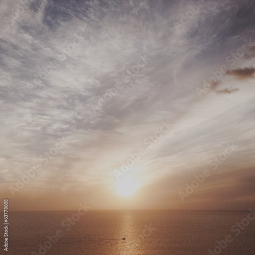 Small boat sailing in sunset