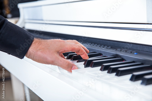 Hand playing white piano