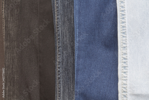 The multi-colored jeans hanging in a row, close up. Background