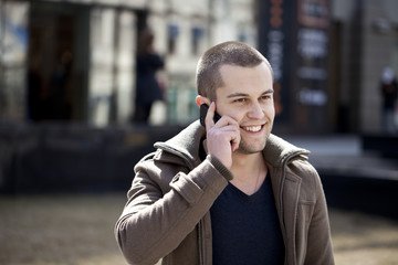 Young attractive man calling by phone