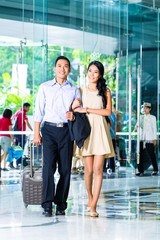 Asian couple arriving in hotel lobby