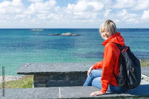 Happy woman enjoying sea / ocean / fjord view