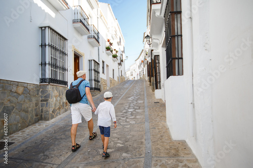 Father and his son walking outdoors in city