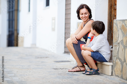 Young mother and her son having rest outdoors