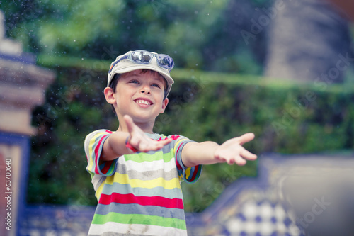Boy playing in the rain during summer time