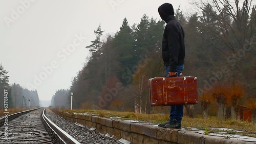 Teenage boy with a suitcase on the platform at the railway