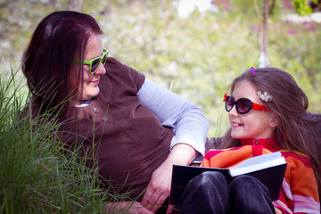 happy mother with adorable little girl reading book