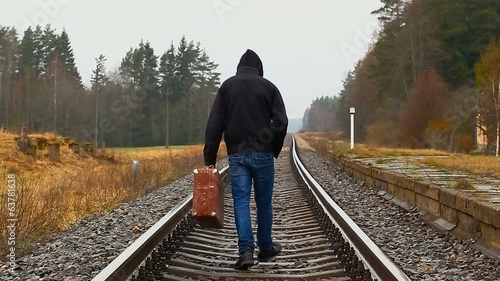 Boy with suitcase go away on rails