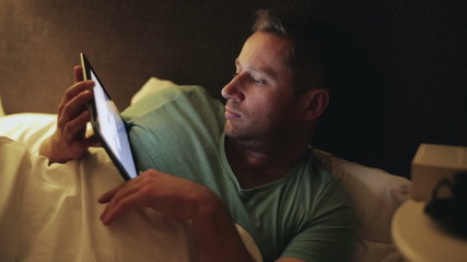 Man lying in bed at night and watching movie on tablet