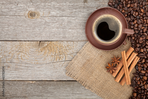 Coffee cup and spices on wooden table texture