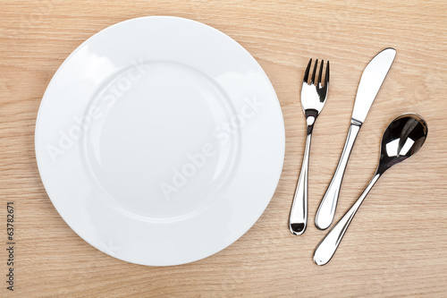 Empty white plate with silverware on wooden table