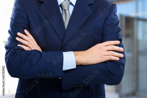Unrecognizable businessman with folded arms