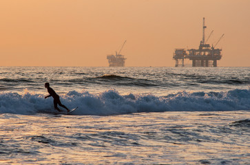 surfing on huntington beach with oil rigs in background
