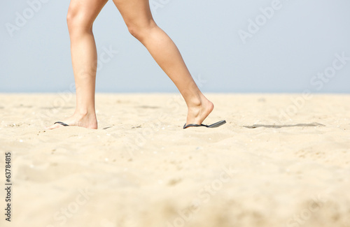 Woman walking in sandals on sand