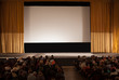 Audience in an auditorium in front of white cinema screen