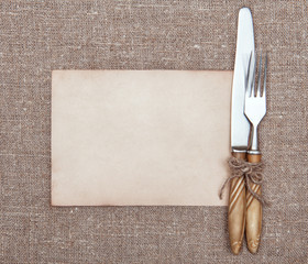 Fork, knife and old paper on the burlap