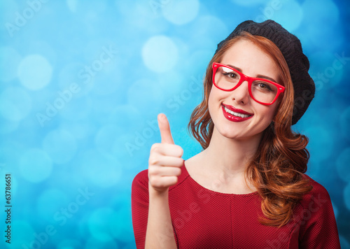 Redhead women in beret on blue background.