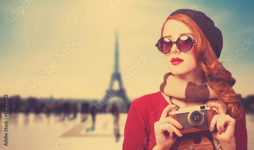 Redhead girl with camera on Paris background.