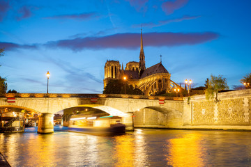 Notre Dame cathedral  with boat on Seine in Paris, France