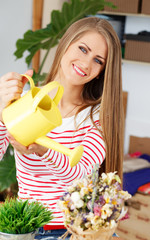 Lifestyle. Attractive girl with watering can