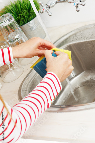 Kitchen. Woman washes tea cup