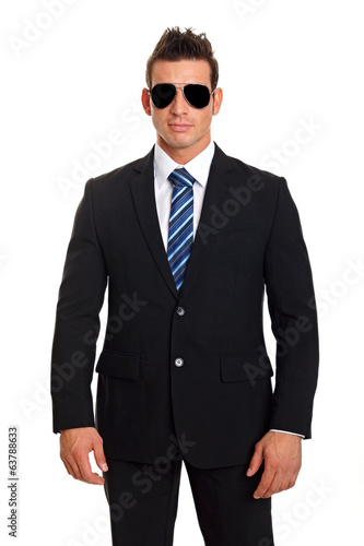 Handsome businessman standing in suit with sunglasses