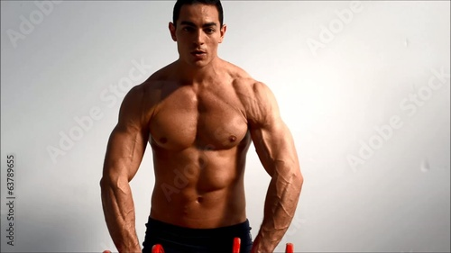 Young handsome male bodybuilder training shoulders with dumbbell