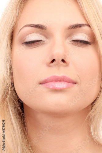 Beautiful young woman's face on white backgroun close-up