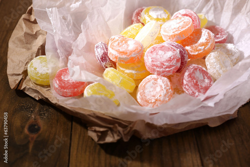Sweet  multicolor candies on paper, on wooden background