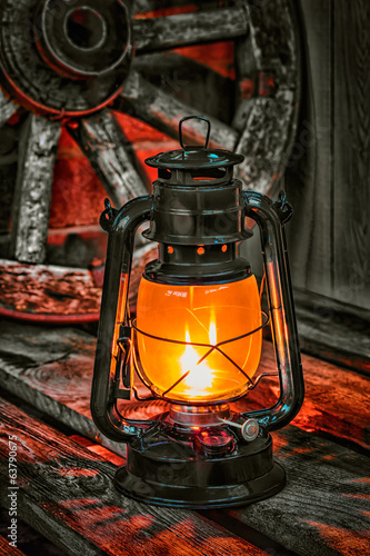 kerosene lamp  against the background wagon wheel