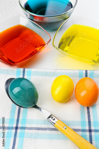Bowls with paint for Easter eggs and eggs, close up