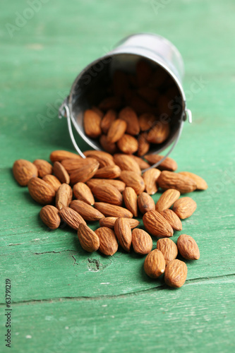 Almonds in bucket on color wooden background