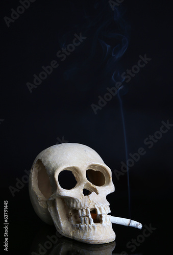 Skull with cigarette isolated on black