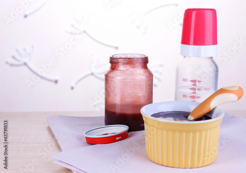 Baby food and milk on table on light background