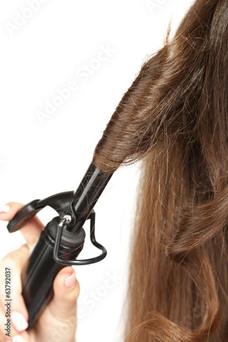 Young beautiful girl doing hairstyle, close up, isolated